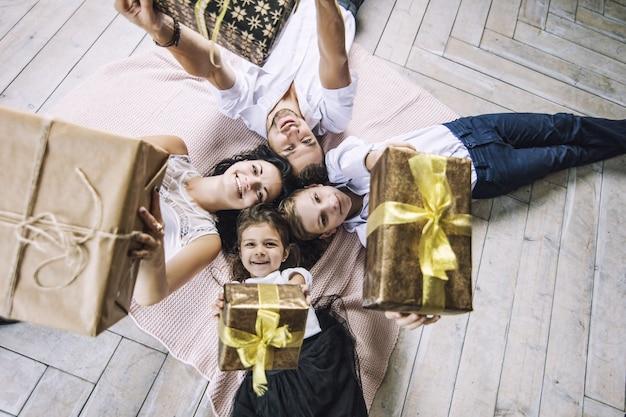 Linda família feliz, mãe, pai, filho e filha com presentes nas mãos estão no chão