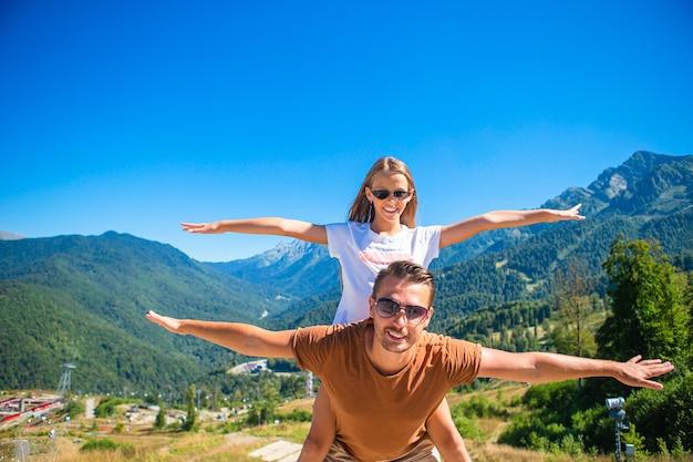 Linda família feliz nas montanhas ao fundo