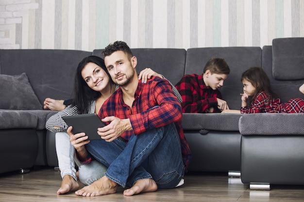 Linda família feliz pai, mãe, filho e filha juntos em casa com um tablet sentado na sala de estar