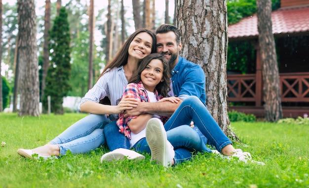 Linda família feliz sentados juntos na grama e se abraçando