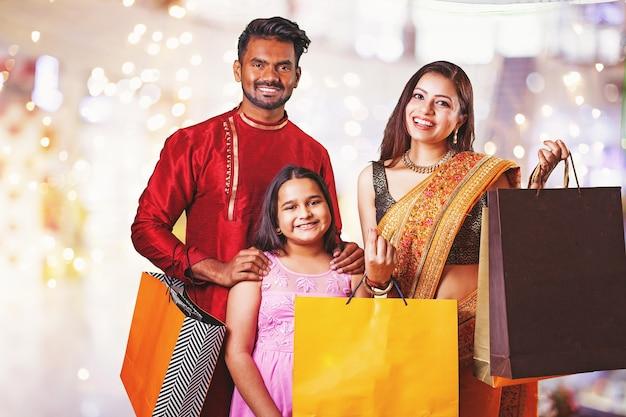Linda família indiana segurando sacolas de compras com presentes em um shopping