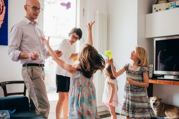 Linda família indoor brincando com brinquedos de balão