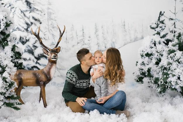Linda família jovem beija seu filho na zona de fotos de inverno