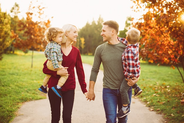 Linda família jovem caminhando no parque e se divertindo com as crianças