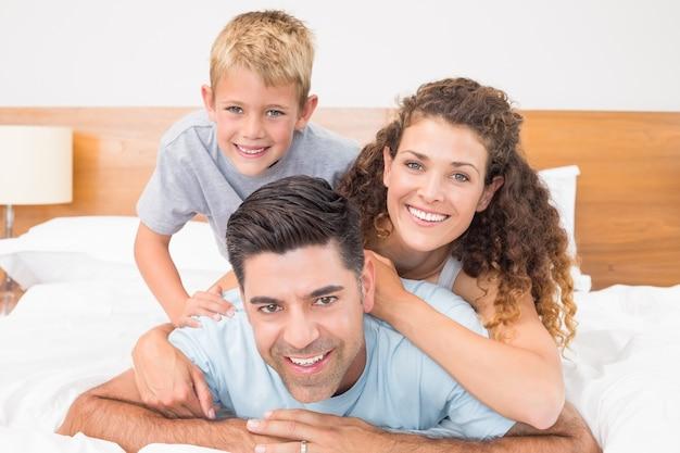 Linda família jovem sorrindo para a câmera na cama posando