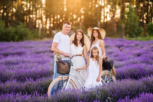Linda família mãe pai e suas filhas em um campo de lavanda com uma bicicleta. fotos de verão sob os raios do sol da tarde.