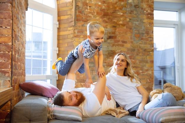 Linda família passando um tempo junta, deitada no sofá