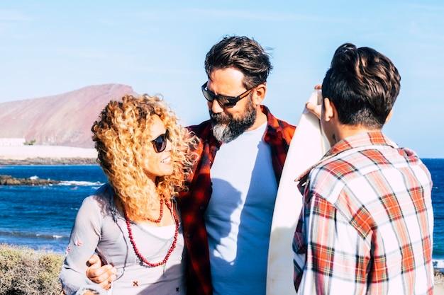 Linda família reunida para sempre na praia com um dia de sol e um adolescente surfista - conversando com a mesa de surf e pessoas felizes - férias de verão - vista traseira