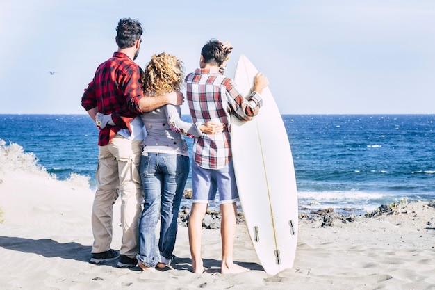Linda família reunida para sempre na praia com um dia de sol e um adolescente surfista - olhando o mar e o céu com mesa de surf e gente feliz - férias de verão - vista traseira