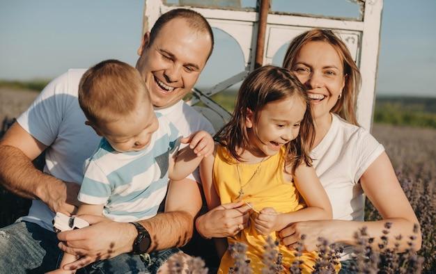 Linda família sorrindo enquanto segura seus filhos em um campo de lavanda durante um dia ensolarado de verão