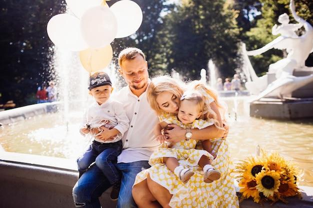 Linda família vestida com a mesma roupa fica na fonte com seus filhos e balões amarelos