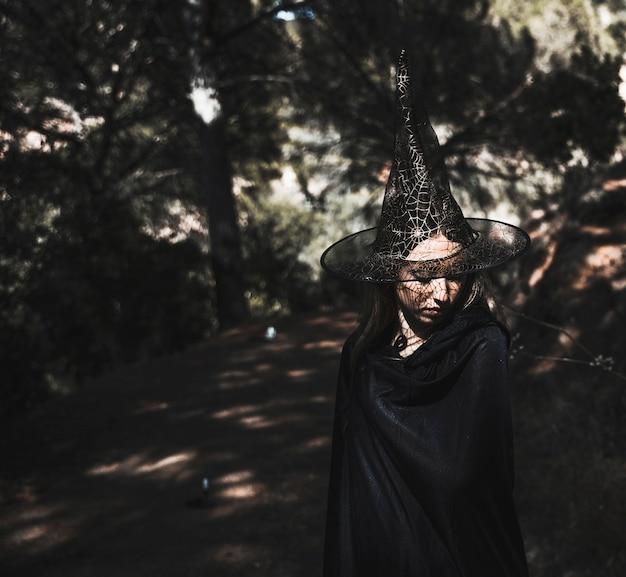 Linda feiticeira no bosque iluminado pelo sol