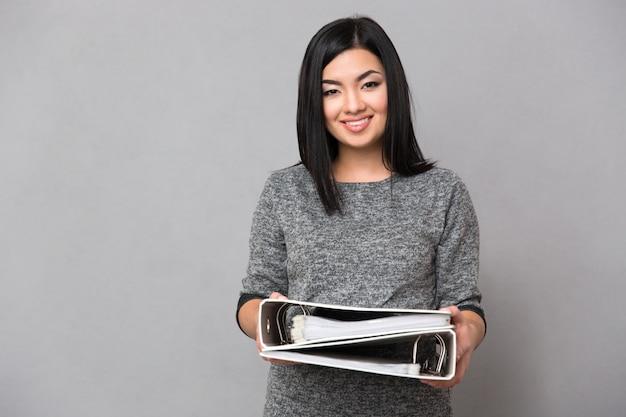 Linda feliz e sorridente mulher asiática em um macacão cinza olhando para frente segurando documentos em duas pastas