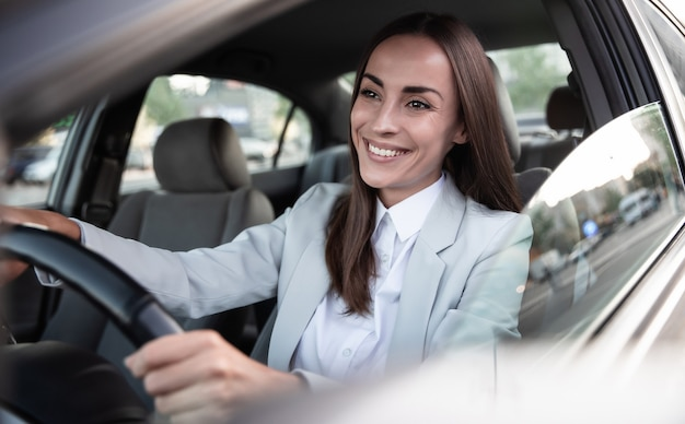 Linda feliz empresária bem-sucedida está dirigindo um carro novo e moderno de bom humor. retrato fofo motorista mulher dirigindo carro com cinto de segurança