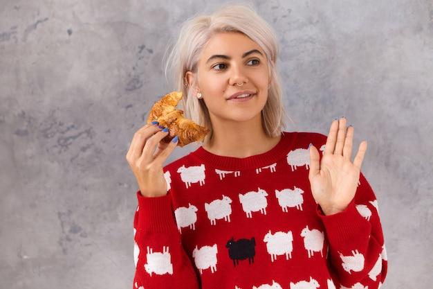Linda feliz faminta jovem europeia com roupas elegantes, saboreando um croissant crocante recém-assado, sentada isolada no café contra a parede em branco, acenando com a mão para chamar a atenção do garçom
