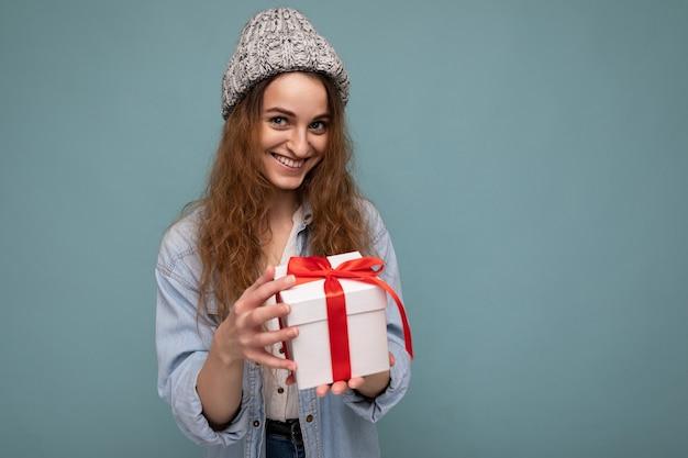 Linda feliz jovem loira escura isolada sobre a parede colorida, vestindo roupas casuais elegantes, segurando uma caixa de presente e. espaço livre