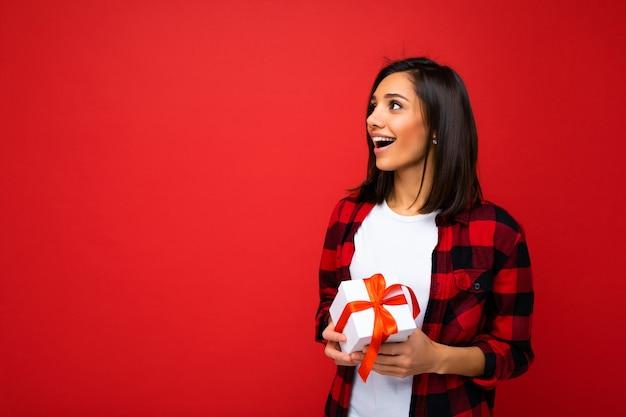 Linda feliz jovem morena isolada sobre a parede de fundo colorido, vestindo roupas casuais elegantes, segurando uma caixa de presente e olhando para o lado. espaço livre
