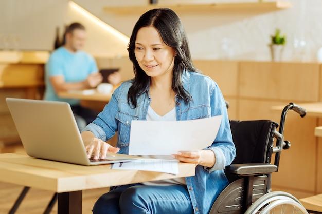Linda feliz mulher aleijada de cabelos escuros sentada em uma cadeira de rodas, segurando uma folha de papel e trabalhando em seu laptop