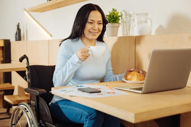 Linda feliz mulher aleijada de cabelos escuros sentada em uma cadeira de rodas, segurando uma xícara de café e trabalhando em seu laptop em um café