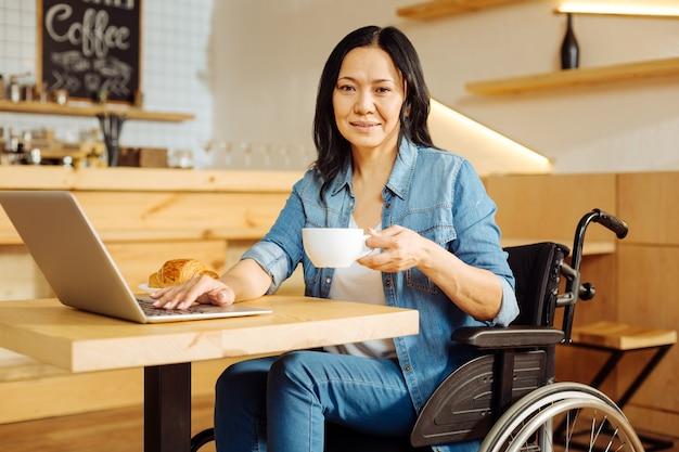Linda feliz mulher aleijada de cabelos escuros sentada em uma cadeira de rodas, segurando uma xícara de café e trabalhando em seu laptop