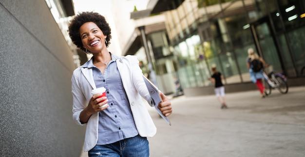 Linda feliz mulher de negócios profissional sorrindo feliz com tablet ao ar livre