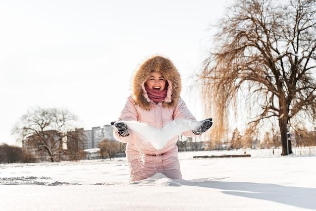 Linda feliz rindo jovem com chapéu de inverno, lenço coberto com flocos de neve. estilo de vida ativo. fundo de paisagem de floresta de inverno.