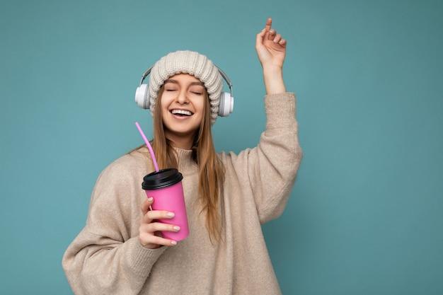 Linda feliz sorridente jovem loira vestindo um suéter bege de inverno e um chapéu isolado sobre o azul
