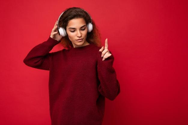 Linda feliz sorridente jovem morena encaracolada, vestindo um suéter vermelho escuro isolado sobre o vermelho