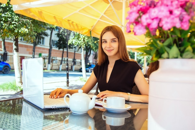 Linda feliz sorridente jovem mulher branca, sentada em um café de rua em uma mesa e trabalhando em um laptop. o conceito de trabalho remoto, freelancer e ensino à distância online.