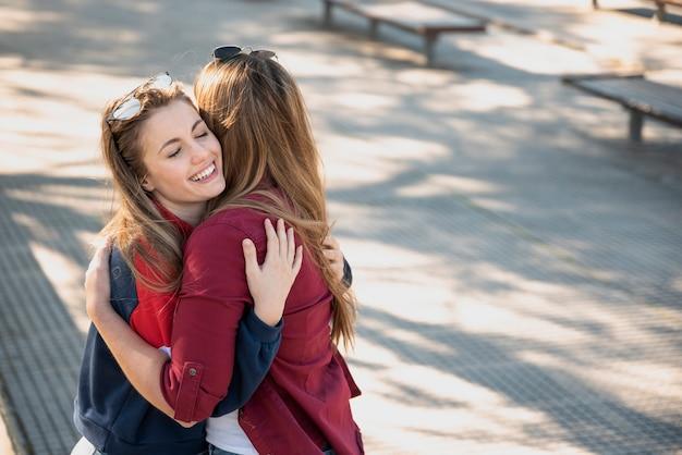 Linda fêmea abraçando na rua