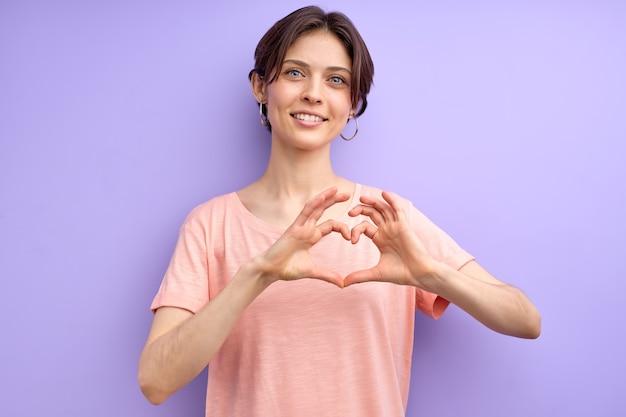 Linda fêmea adulta expressando amor e amizade, fazendo formato de coração com as mãos e olhando para a câmera, sorrindo, em uma camiseta rosa casual. tiro isolado. copie o espaço