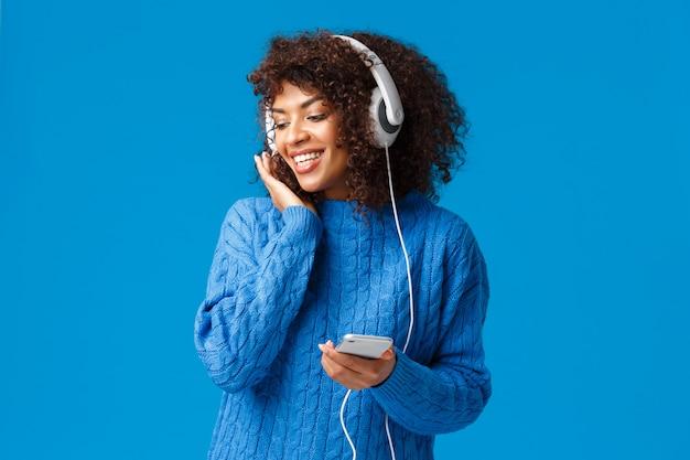 Linda fêmea afro-americana bonita camisola de inverno, ouvindo música romântica