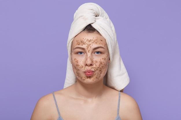 Linda fêmea com máscara no rosto, mantém os lábios arredondados, posa com uma toalha branca na cabeça