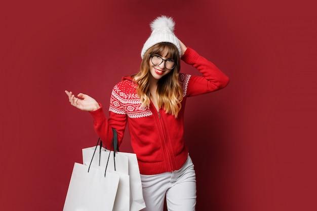 Linda fêmea de chapéu de lã branca e blusa vermelha de inverno posando com sacolas de compras