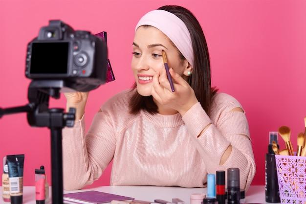 Linda fêmea grava vídeo. yong blogger mostra como aplicar sombra. lady advetises cosméticos em seu canal