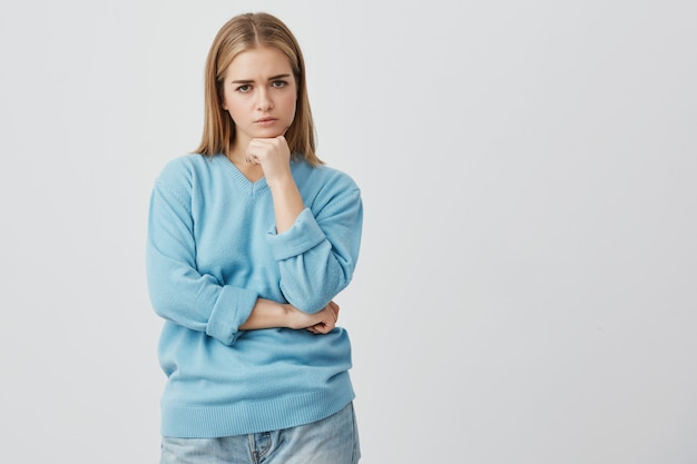 Linda fêmea insatisfeita caucasiana com cabelos lisos lisos, vestindo roupas casuais, olhando com raiva, segurando as mãos sob o queixo, insatisfeita com as ações do namorado.