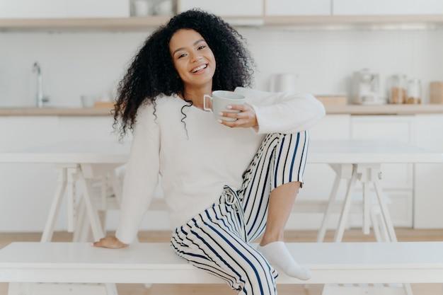 Linda fêmea jovem com corte de cabelo afro, coloca no banco branco interior, vestido com roupas elegantes