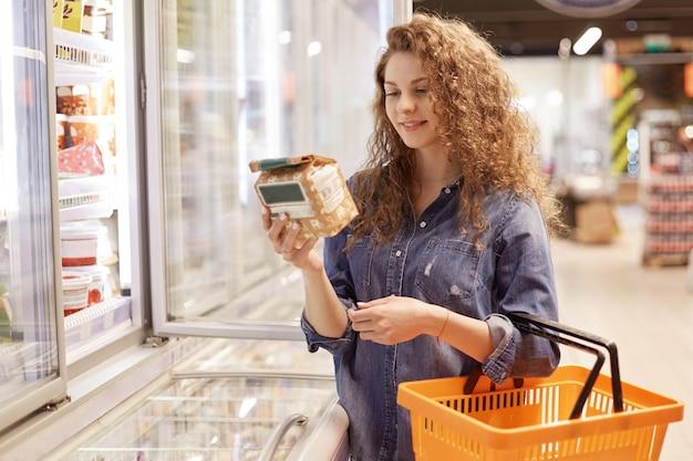 Linda fêmea jovem com expressão satisfeita, segura o carrinho de compras, lê o produto abpput de informações, fica perto da geladeira no supermercado, escolhe os itens necessários para preparar um delicioso jantar