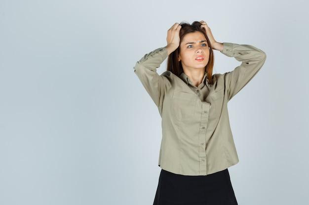 Linda fêmea jovem em camisa, saia de mãos dadas na cabeça e parecendo confusa, vista frontal.