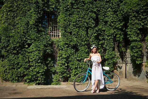 Linda fêmea jovem posando perto de bicicleta turquesa em frente a parede do jardim de hera vertical durante o dia ensolarado de verão