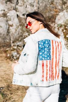 Linda fêmea na jaqueta jeans e óculos de sol