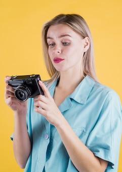 Linda fêmea segurando a câmera tiro médio