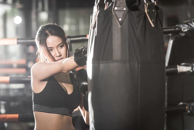 Linda fêmea, socando um saco com luvas de boxe no ginásio