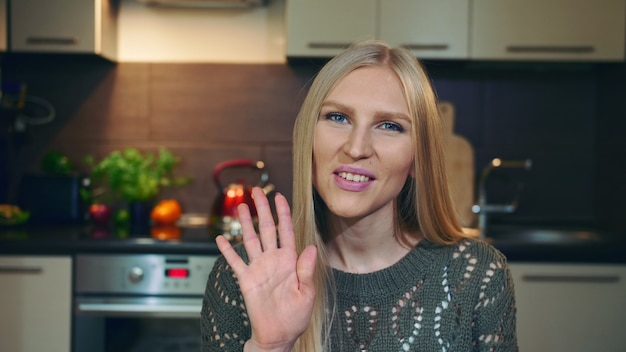 Linda fêmea sorrindo e olhando para a câmera enquanto cumprimenta a audiência do vlog, acenando com a mão no fundo da cozinha elegante.