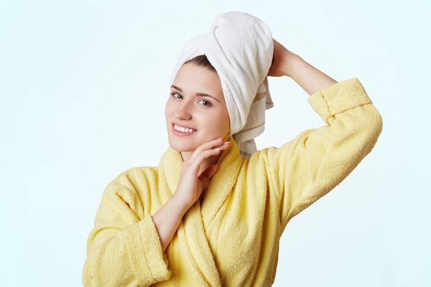 Linda fêmea vestida com túnica amarela e toalha na cabeça