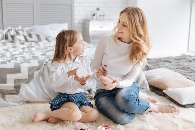 Linda filhinha e sua jovem mãe agradável sentadas no tapete, segurando caixas de pó e falando sobre cosméticos.