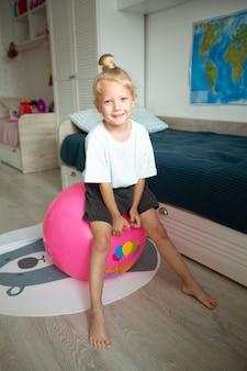 Linda filhinha sentada em uma bola de borracha em casa