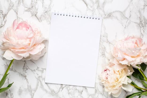 Linda flor de peônia branca e caderno em fundo de mármore