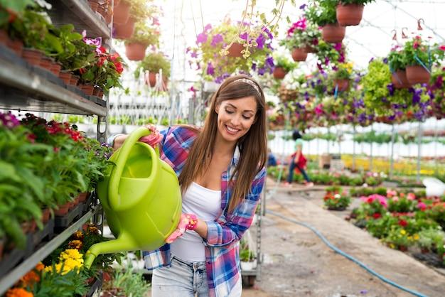 Linda florista feminina regando com regador no centro de jardim.