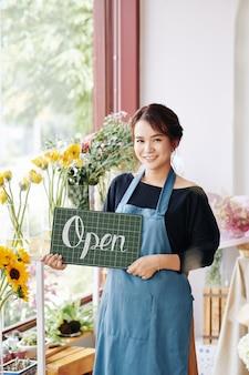Linda florista segurando cartaz aberto